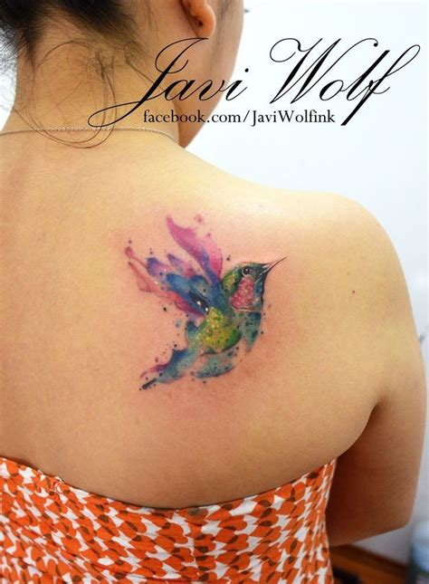 little flying bird watercolor tattoo on upper back