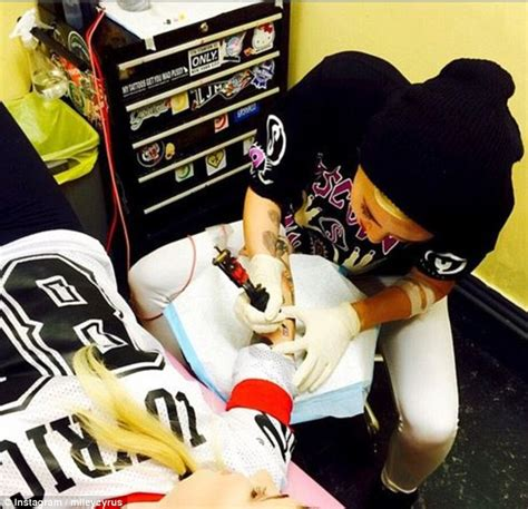 miley cyrus turns tattoist as she and an artist take it in