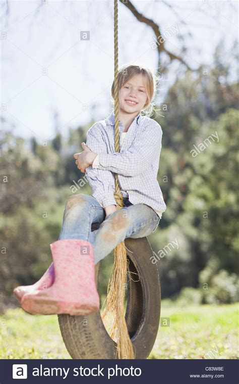 sitting on a swing girl sitting on tire swing outdoors stock photo royalty