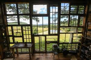 artist built a cabin made of recycled windows in
