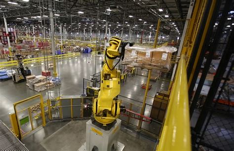 amazon warehouse robots hands heads and robots work in sync at amazon warehouses