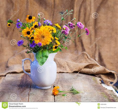 flowers on table bouquet of flowers in a white vase on a wooden table stock