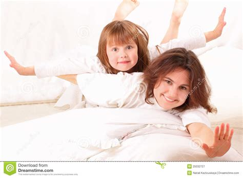 two girls in bed two happy girls lying in bed royalty free stock