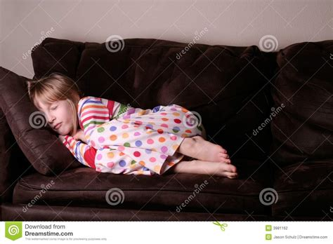 curled up on the sofa cozy asleep in pajamas on sofa stock photography image