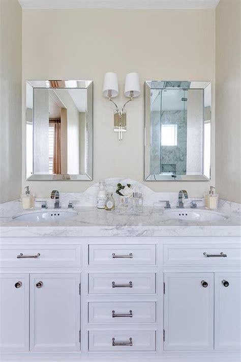 curved marble dual vanity backsplash  beveled mirrors transitional bathroom