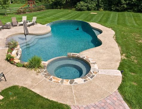 inground swimming pool with tanning ledge and spa