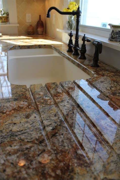 kitchen sink built into countertop drain board built into a granite countertop leading to a