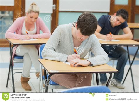 Students In Desks Writing Students At Desks In A Classroom Royalty Free