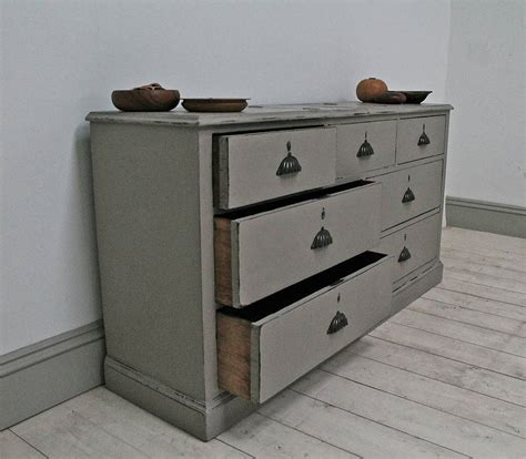 distressed painted bank of apothecary drawers by