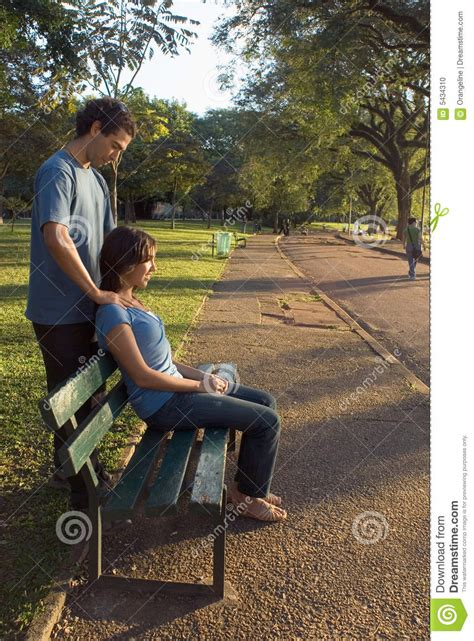 couple on park bench young couple sitting on a park bench vertical stock