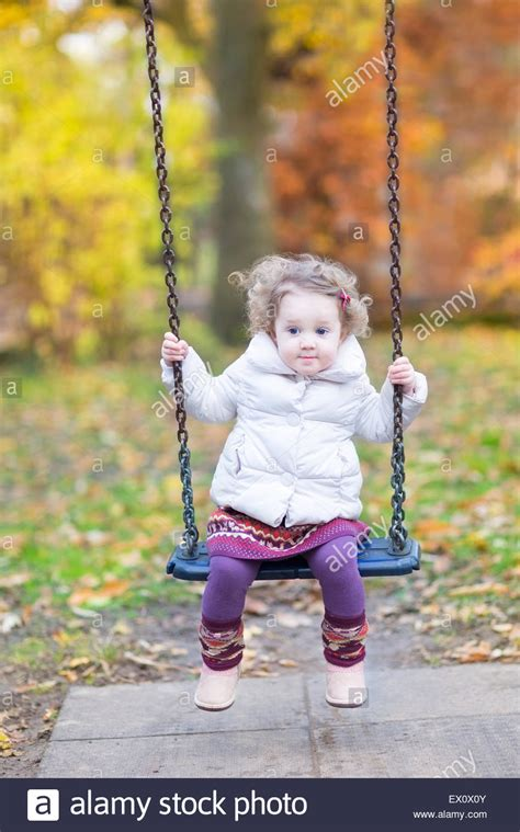 cute baby girl swings cute baby girl playing on a swing with beautiful autumn