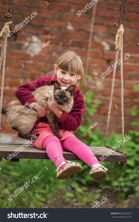 cat on a swing little girl sitting with a cat on the swing stock photo