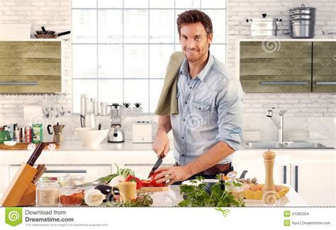 kitchen in a day handsome man cooking in kitchen at home stock photo