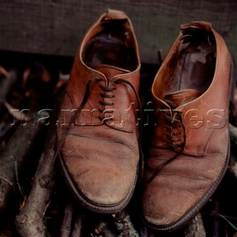 el0259 a pair of worn brown leather shoes on to