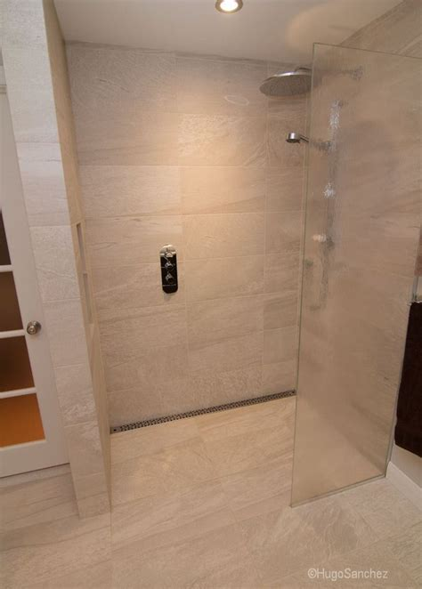 doorless curbless tile shower with river rock floor and stainless steel linear drain grate no threshold shower