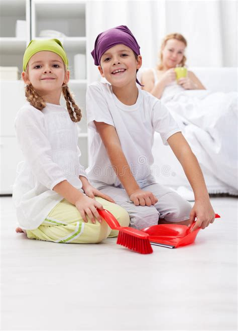 kids cleaning the room helping their mother royalty free