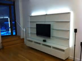 Long white floating media cabinet integrating with glass wall shelves