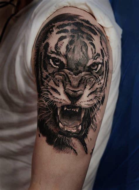 tatuaje de la cabeza de un tigre en el brazo izquierdo