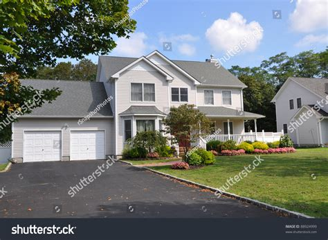 suburban two car garage large siding home with double wide