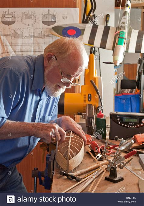 boat making older man retiree making model boat in workshop uk
