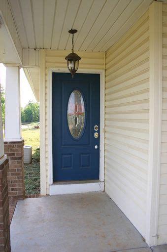 light yellow siding white trim  dark blue door
