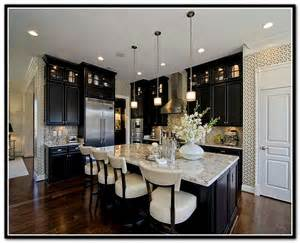 black kitchen cabinets with white marble countertops kitchen with granite counters and a white finish griffin