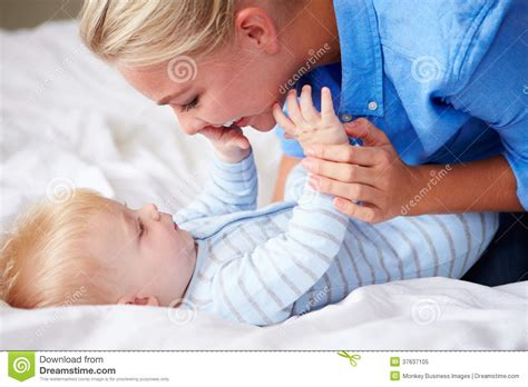lie in bed mother playing with baby son as they lie in bed together royalty free stock photo