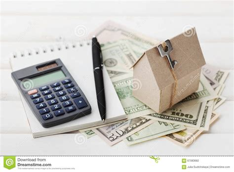 house building loan calculator model of cardboard house with key calculator notebook pen and cash dollars house