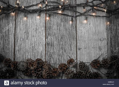 rustic background lights and pine cones on rustic wood background