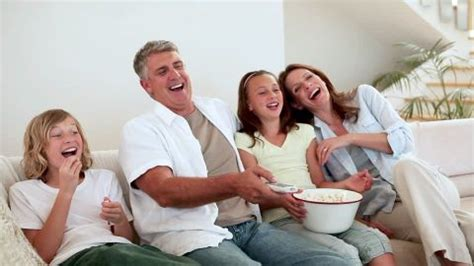 family watching tv with popcorn in living room stock photo family watching tv home hd stock video footage