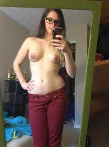 sexy chick with glasses and red pants is standing without anything on