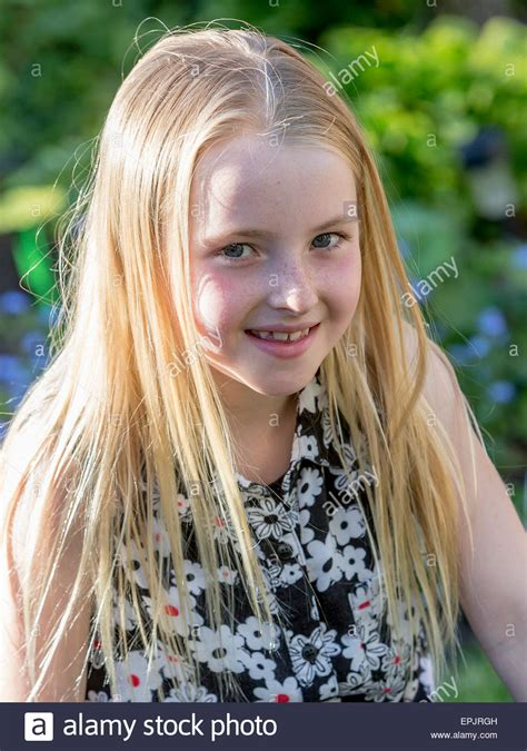 8year oldeer hair blonde 8 year old girl sitting in a garden posing for the