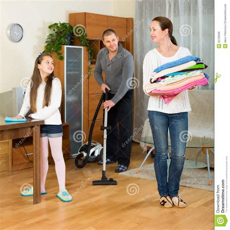 cleaning up room family of three tidying up a room stock photo image