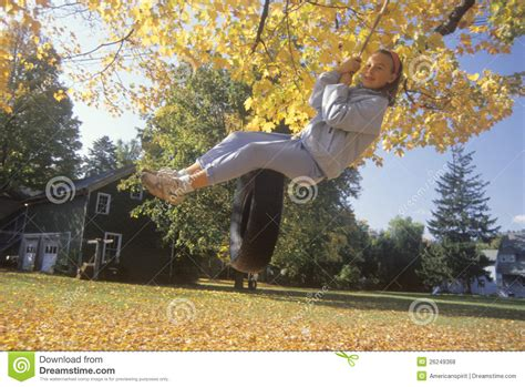 swinging new england a girl on a tire swing in autumn editorial stock photo