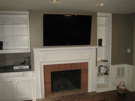 fireplace mounting tv above fireplace with shelving unit