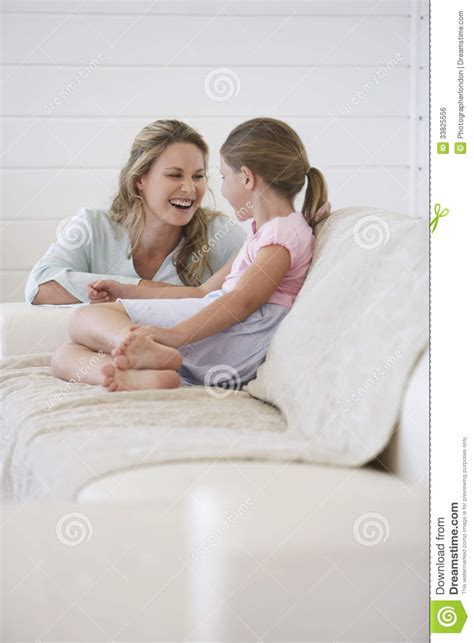 mom on sofa mother crouching next to girl sitting on sofa royalty free