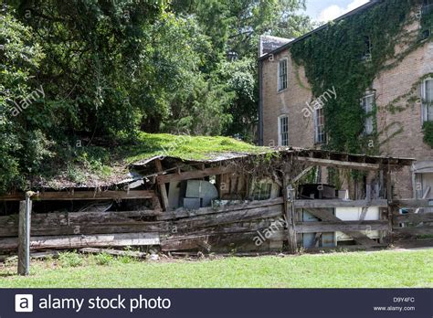 ram shackle brick building and ramshackle shed with a vine covered