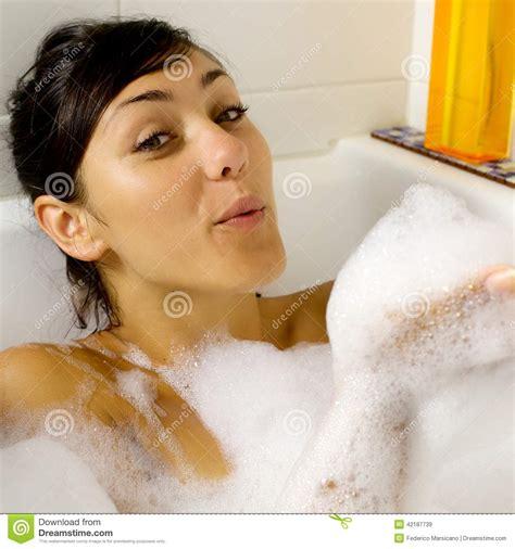 schiuma vasca da bagno donna felice gioca con la schiuma in vasca da bagno