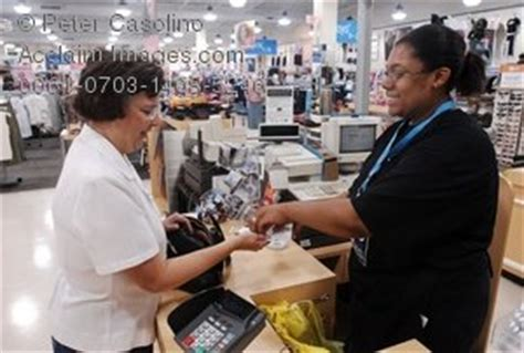 photo of a store clerk at sales counter at retail clothing chain store acclaim stock photography
