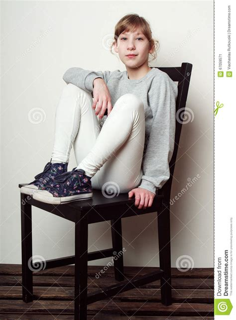little girl on chair little girl is sitting on the chair smiling stock