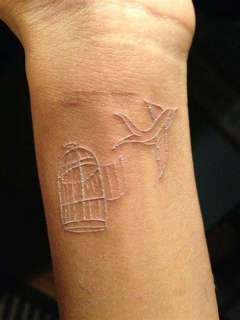 small bird cage tattoo flying bird from cage white ink on wrist