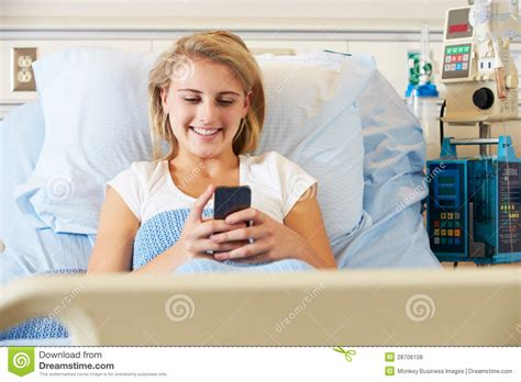 smiling girl using mobile phone in bed royalty free stock teenage female patient using mobile phone in hospital bed