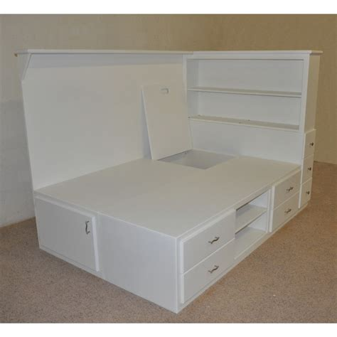 white wooden bed with many storage drawers combined with shelves on the head board placed on the