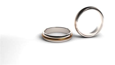 studio shot of two wedding rings falling against white