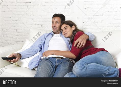 making love on the sofa couple in love cuddling on home couch relaxing watching