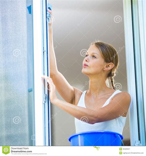 washing house windows pretty young woman doing house work washing windows royalty free stock photography