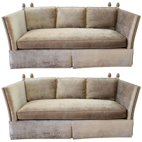 pair of knoll style sofas with acorn finials in chagne