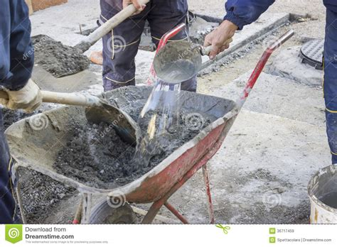 Cement House Plans workers mixing the cement by hand in wheelbarrow 2 royalty
