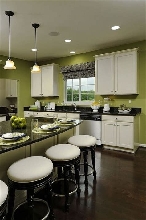 i this kitchen green walls white cabinets black countertops and wood floor