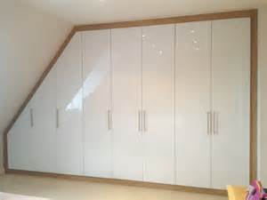 Built in loft wardrobe with acrylic white gloss doors and oak frame